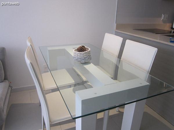 Mesa de comedor en vidrio con cuatro sillas.