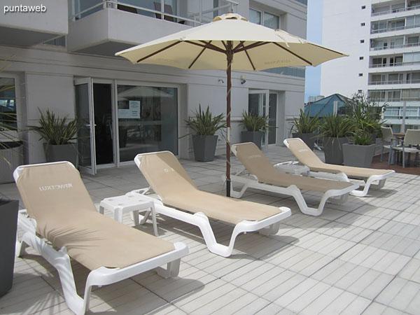 Sombrillas y reposeras en el sector de la pileta al aire libre situado en terraza del segundo piso.
