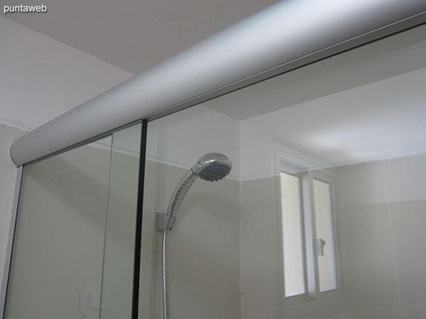 Baño de la suite con ducha y mampara de vidrio.