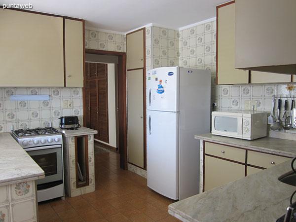 Cocina, amplia, accesible desde el espacio de comedor y del pasillo hacia los dormitorios y dormitorio de servicio.