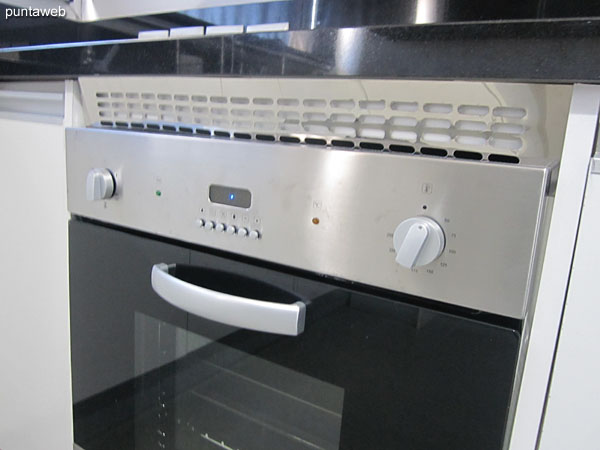 Kitchen equipment detail: four–burner electric stove with extractor hood and built–in electric oven.
