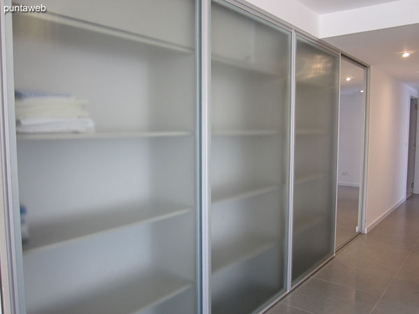 Large wardrobe / closet with glass doors located on the side of access to the living room.