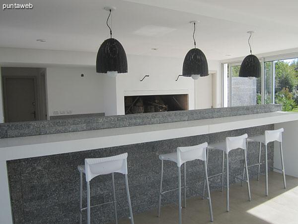 Barra mostrador entre el parrillero y el espacio de comensales en la barbacoa acondicionado con cuatro modernos taburetes.