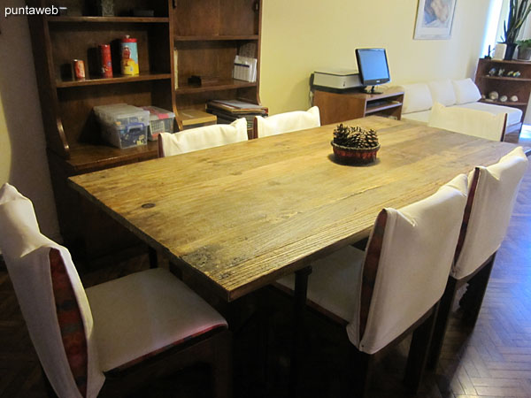 Dining space with rectangular wooden table with six chairs.