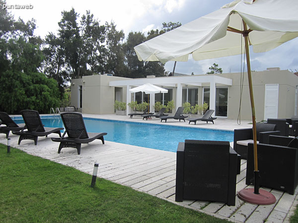 The space surrounding the outdoor pool has lounge chairs, chairs and umbrellas.