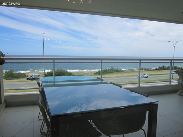 Access to the terrace balcony of the apartment. It has a barbecue, rectangular glass table with six chairs.