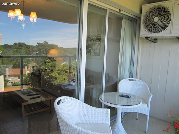 Balcony terrace of the apartment, open and roofed. It has a round table with two chairs.