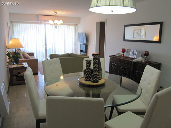 General view of the living room. In the foreground the dining space. Towards the back the living space and access to the balcony terrace of the apartment.