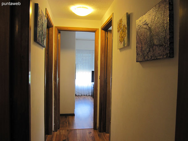Hallway to the bedrooms with a door to the living room.