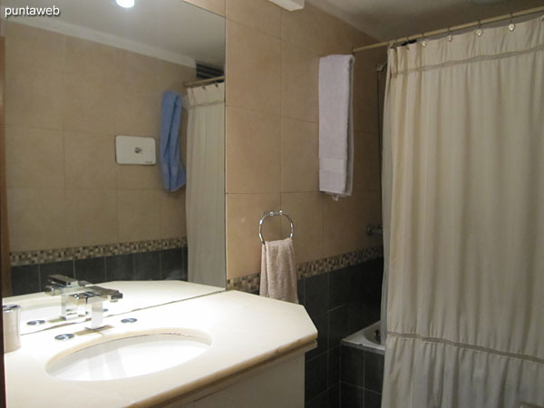Second bathroom Shared bathroom between the second and third bedrooms. It has a shower, shower curtain and bathtub.
