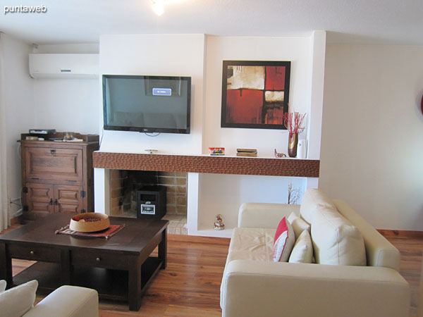 Living environment in the living room. It has TV with cable, air conditioner, armchair of two bodies and armchair of three bodies in L around a low table in wood.