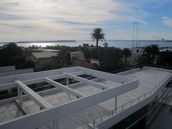 Vista de las terrazas desde la ventana del gimnasio en el último piso. Al fondo, la piscina al aire libre, el puerto y la bahía de Punta del Este.