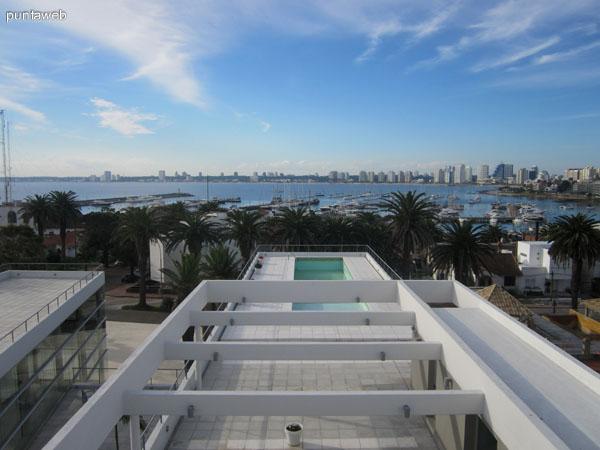 Vista desde la terraza hacia el norte. Al fondo se aprecia la piscina al aire libre y la bahía de Punta del Este con el puerto de yates en primer plano.