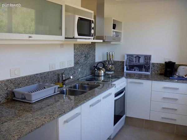 Cocina con mesada en L de granito, muebles sobre y bajo mesada de nivel, equipada con electrodomésticos de igual perfil.