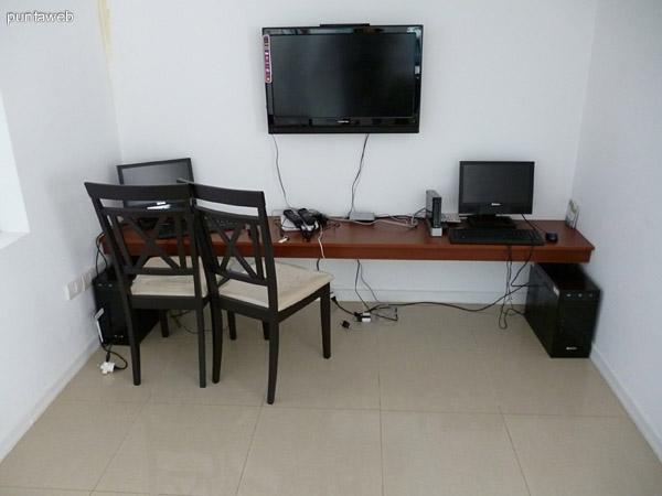 Consola de videojuegos y computadora en sala de juegos.
