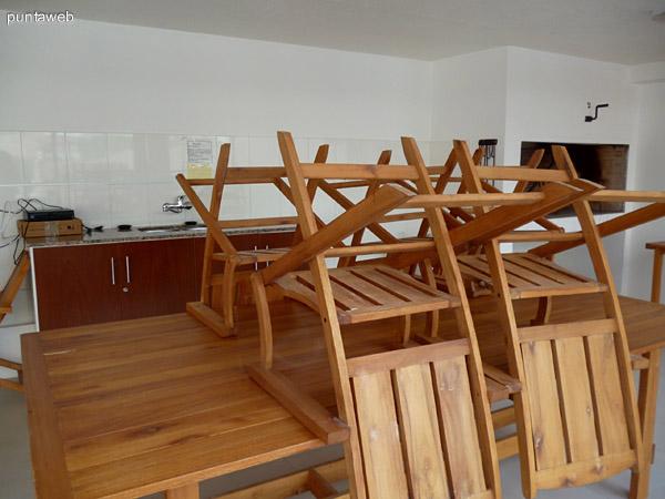 Salón común con 2 parrilleros, mesas, sillas y heladera.