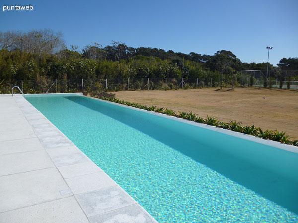 Hermosa piscina próxima a cancha de tenis y campo de golf.