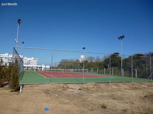 Cancha de tenis cercada e iluminada.