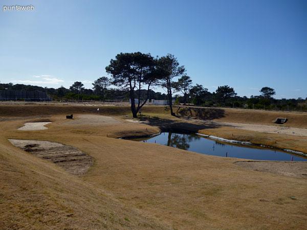 Campo de golf con laguna artificial.