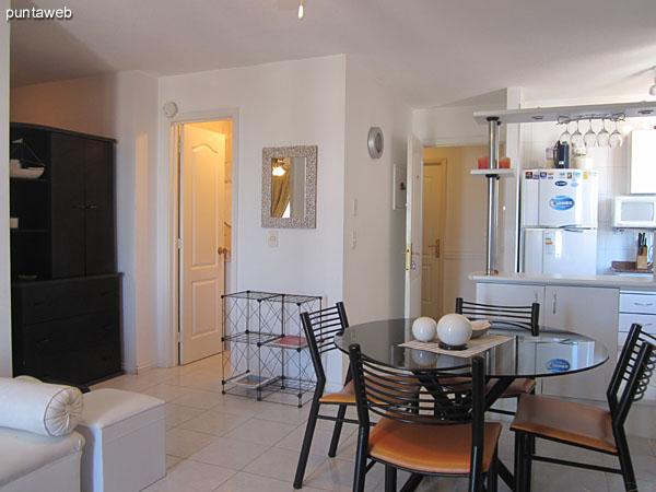 Vista general del ambiente de living comedor integrado a la cocina a través de una barra en primer plano.