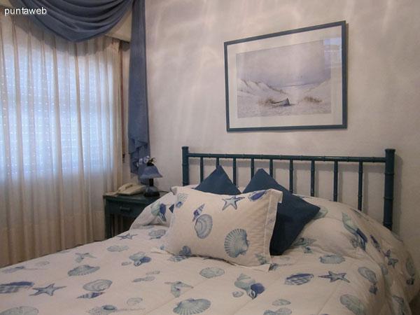 Sofá cama dispuesto en ambiente que conecta el living con el dormitorio y el baño visto desde el final del pasillo de acceso.