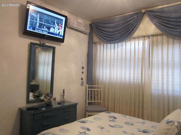 Dormitorio. Acondicionado con cama matrimonial y televisor de pantalla plana. La ventana ofrece vistas al oeste y suroeste sobre la península de Punta del Este y la playa El Emir.
