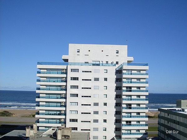 Vista al mar entre edificios, desde la segunda fila del apartamento.
