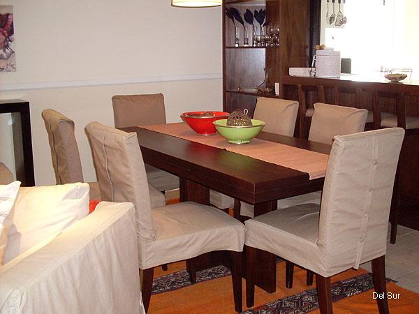 Mesa de comedor en madera con seis sillas en madera, forradas con tela.