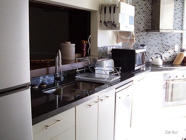 Cocina con pasaplatos, comunicada al comedor y lavadero incorporada.