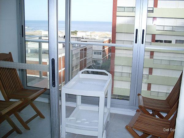 Terraza exterior con cerramiento de vidrio y aluminio, con muebles de terraza.