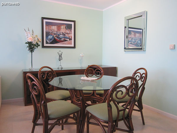 Dining space located to the right of admission.<br><br>Conditioning with round wood and glass table with five chairs.
