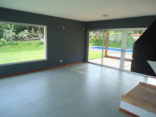 Vista del espacio del living comedor con estufa a leña y grandes ventanales circundantes en aluminio.