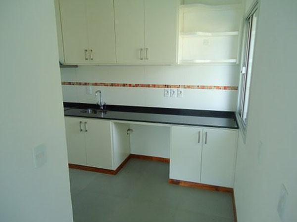 Cocina con mesada, muebles bajo y sobre mesada, espacio para anafe y campana extractora. A la izquierda mueble con horno empotrado.