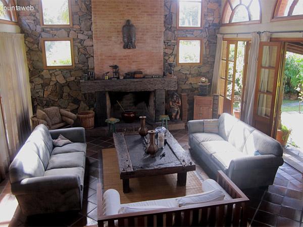 Vista desde el living a nivel de sof� hacia el fondo de la casa. Se aprecia el jard�n y el parrillero con casa de hu�spedes.