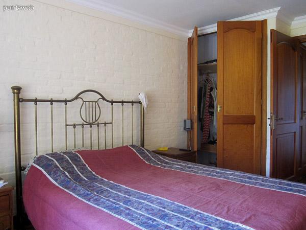 Dormitorio principal en planta baja. Placares de madera y gran ventana al frente de la casa.