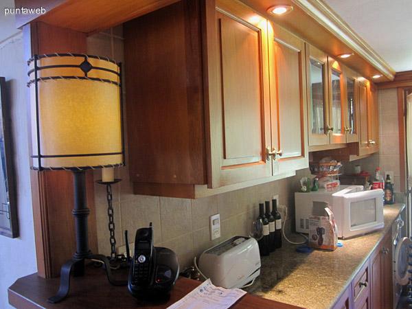 Vista del comedor desde la cabecera de la mesa hacia la cocina. Al fondo, el toilette.
