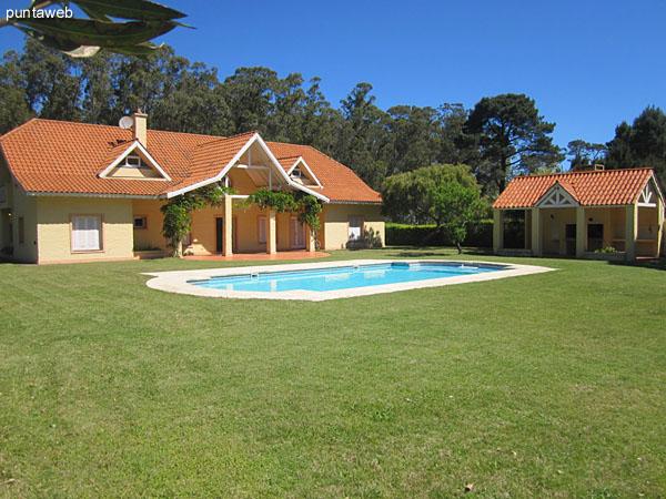 Contrafrente de la casa orientado al norte. Amplio jardín con piscina.
