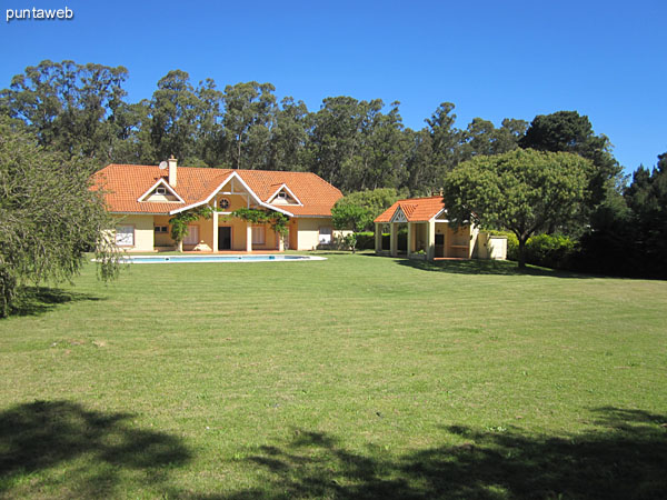 The building of the house facing north. Large garden with pool.