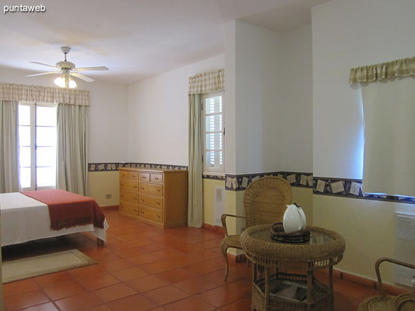 The main floor bedroom has a conditioned environment with rattan round table and two chairs.