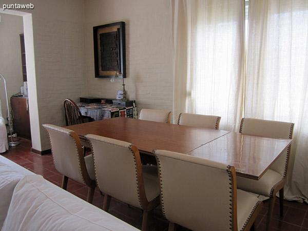 Espacio de comedor en el lateral del ambiente. Acondicionado con importante mesa rectangular con seis sillas tapizadas a juego.