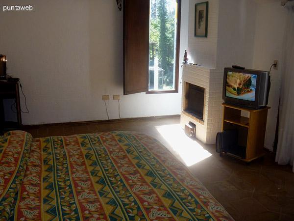 TV y estufa a leña en el dormitorio.