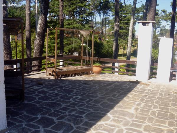 Terraza con reposeras. Entorno con muchos pinos marítimos.