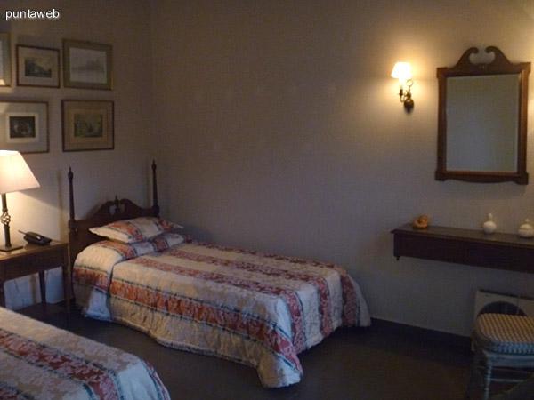 Dormitorio con dos camas simples. Amplias ventanas con persianas de madera y finos cortinados.