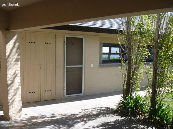 Puerta con mosquitero de la cocina que comunica con el parrillero. Heladera dentro del armario exterior.