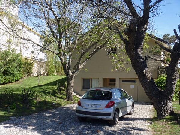 Contrafrente de la casa. Entrada del garage. Espacio para estacionar dos autos dentro de la propiedad bajo la sombra de los árboles.