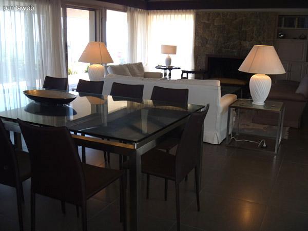 Elegante mesa de vidrio y acero inoxidable con 10 modernas y estilizadas sillas.
