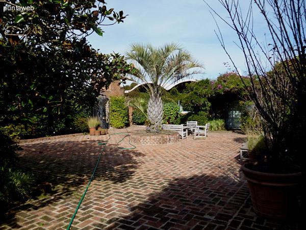 Jardín interior con juego de exterior en madera y banqueta haciendo juego.