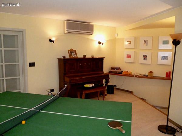 Mesa multiproposito, piano y equipo split frío/calor dentro de las comodidades de la sala.