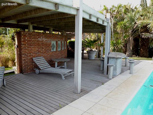 Deck solarium próximo a la piscina, mesa y bancos en madera.<br>Mobiliario de exterior haciendo juego.