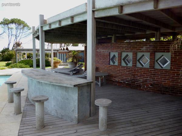 Barra, deck solarium y reposeras próximos a piscina.